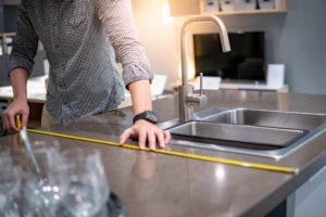 A homeowner measuring their counters to install FeelsWarm countertop heaters.