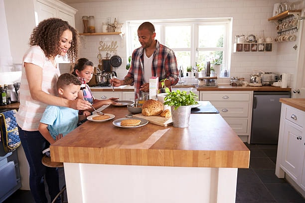 A family cooking at a kitchen island with a thick wooden countertop.