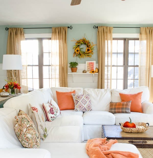 A living room with a white sectional couch with orange pillows.