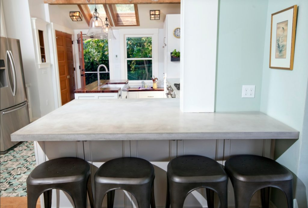 A concrete breakfast bar with metal stools.