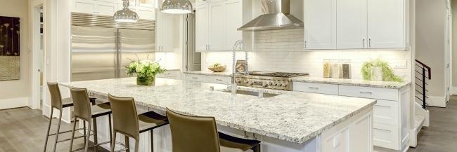 A soft gray granite countertop in a white kitchen.