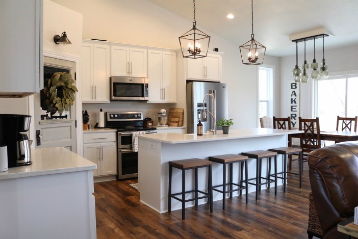 A beautiful kitchen with white cabinets and dark wooden floors.