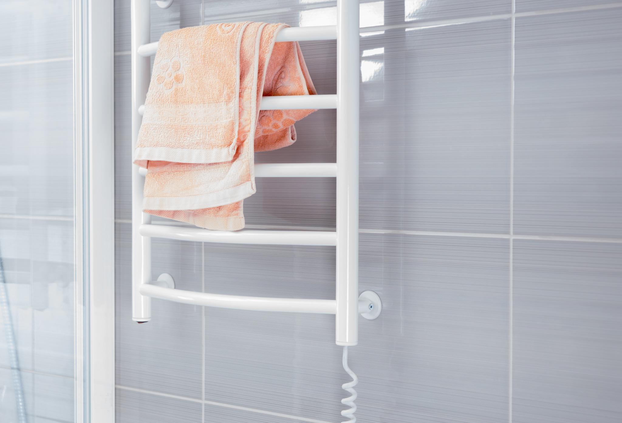 A heated towel rack in a gray tile bathroom.