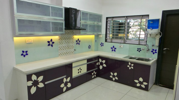 An ugly retro kitchen with flowers painted on the backsplash and cabinets.