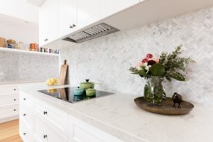 A bright white kitchen with heated counters. Styled with flowers.
