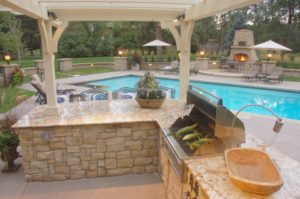 An outdoor kitchen space with a pool.
