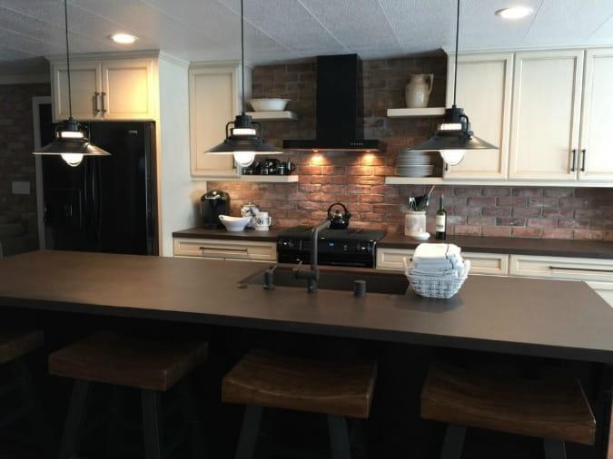 A Kitchen with a dark brick wall and dark brown Dekton countertops.