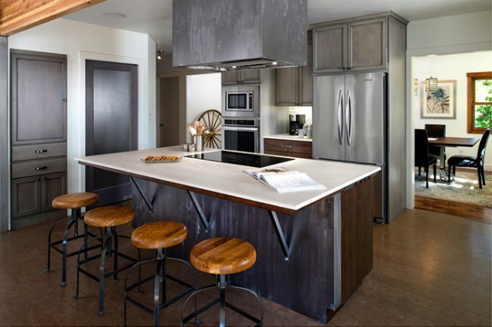 A kitchen with dark grey cabinets and a light-colored kitchen island made of Dekton.