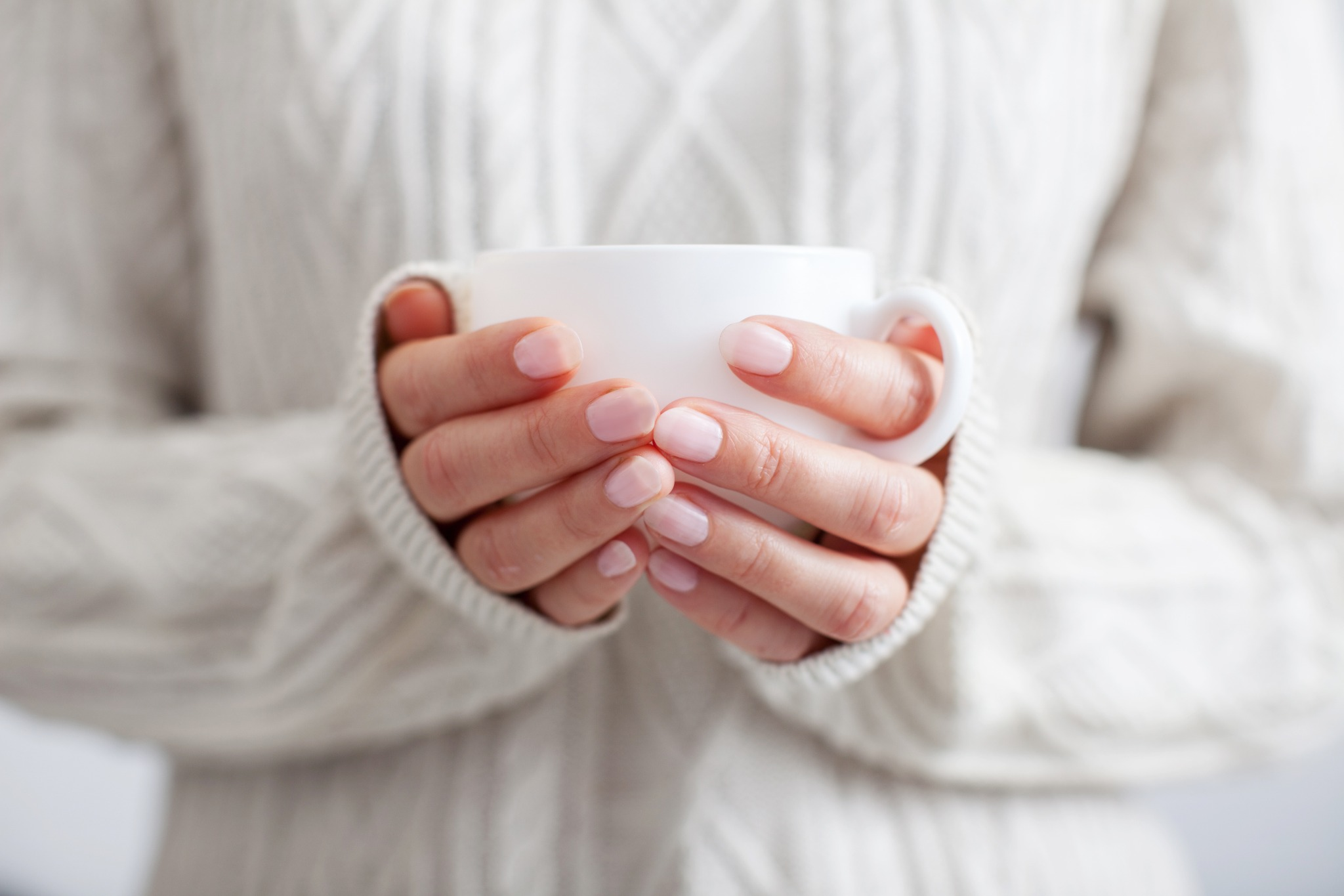 A woman in a sweater holding a white mug to warm her cold hands.