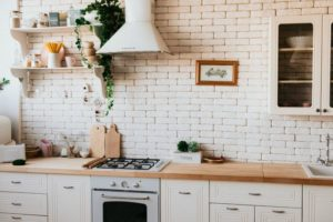 A country-style kitchen with a stone backsplash.