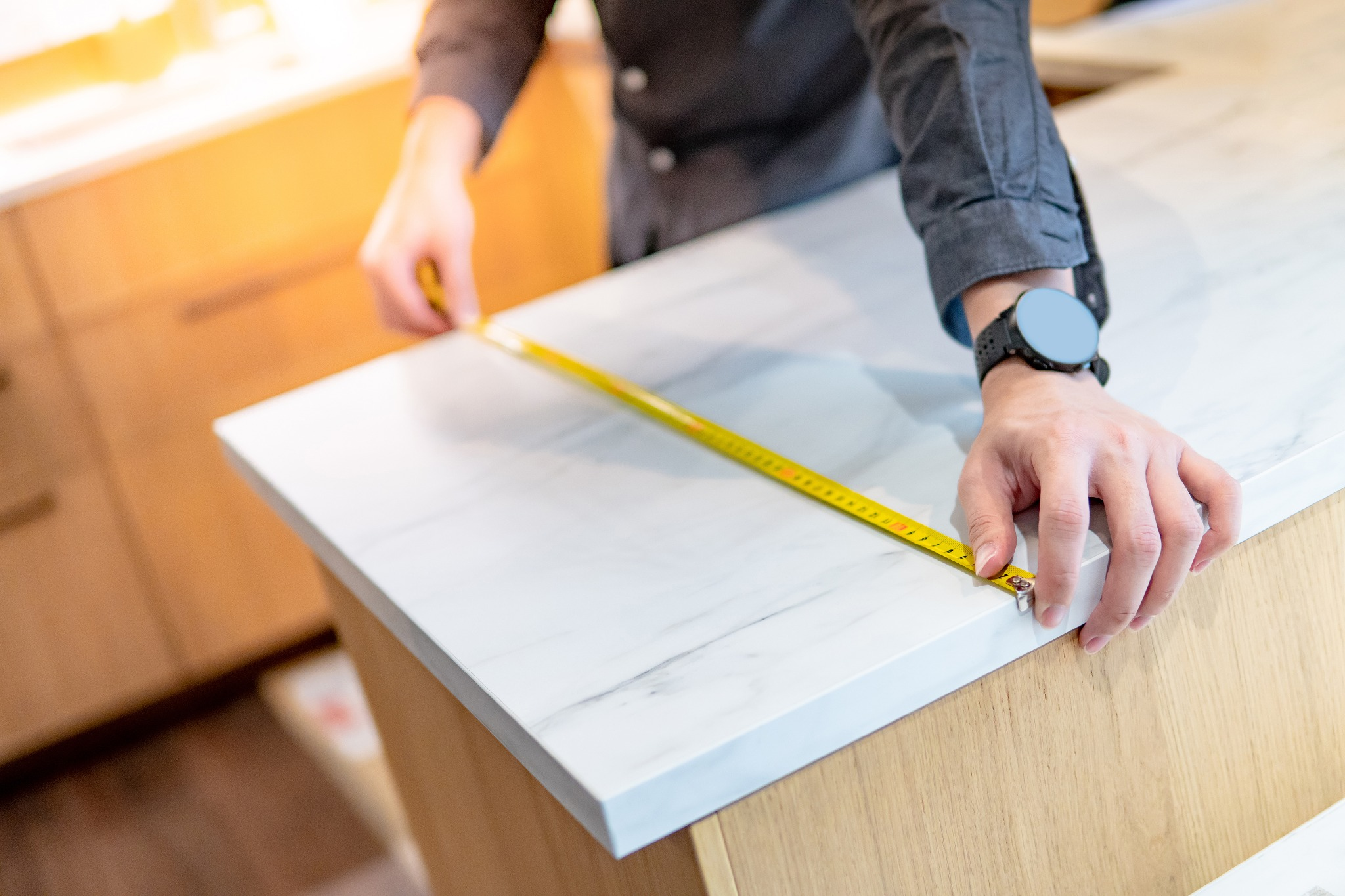 Someone measuring a white countertop in order to install FeelsWarm