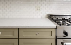 Khaki colored cabinets with white stone counters.