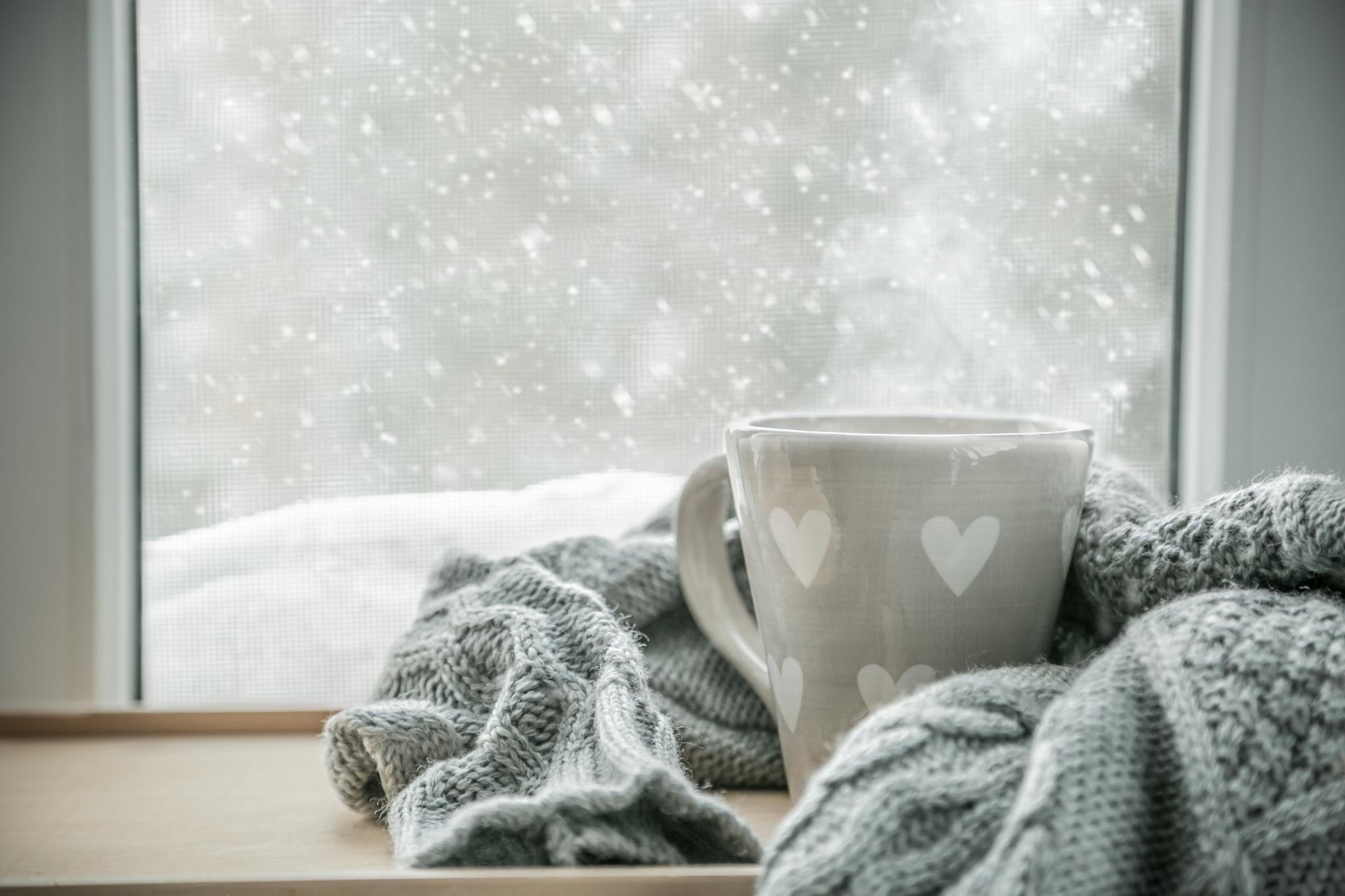 A grey mug with hearts wrapped in a scarf sitting in front of a window with a snowy background.