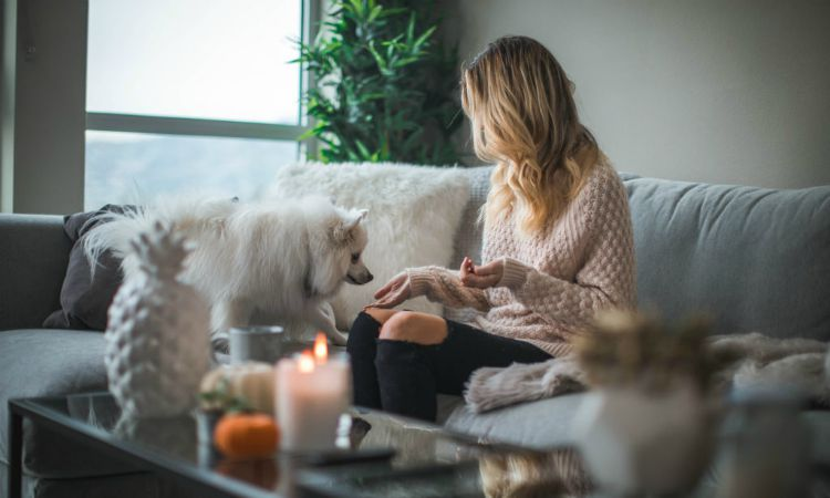 A woman at home with candles lit and her fluffy white dog.