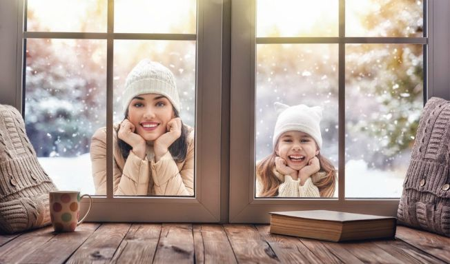 a woman and a young girl outside looking through a window holding their heads up with the hands smiling