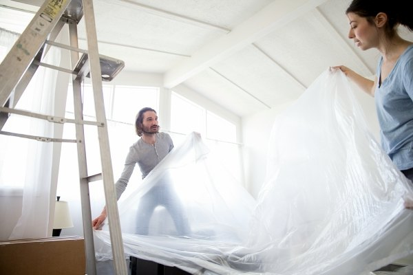 man and woman stretch out a plastic tarp in a room near a ladder