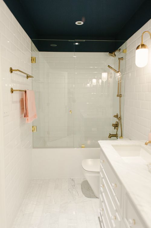 modern bathroom interior with white tile and stone countertop with glass shower wall
