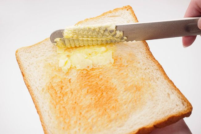 person holding butter knife, spreading butter on toast