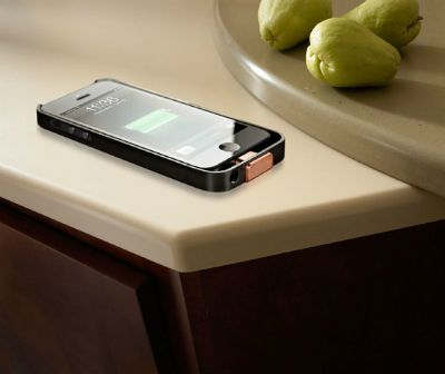 iphone sitting on a counter near some pears
