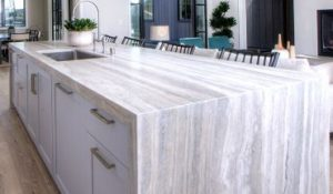 long stone island countertop with white drawers