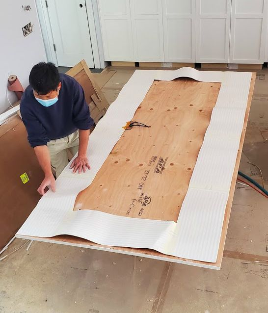 worker sizing wood plank with graphing paper