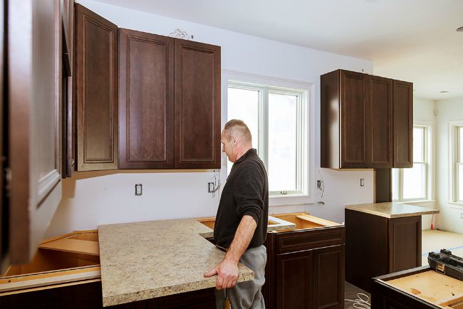 man installing new stone countertop on new kitchen countertop supports