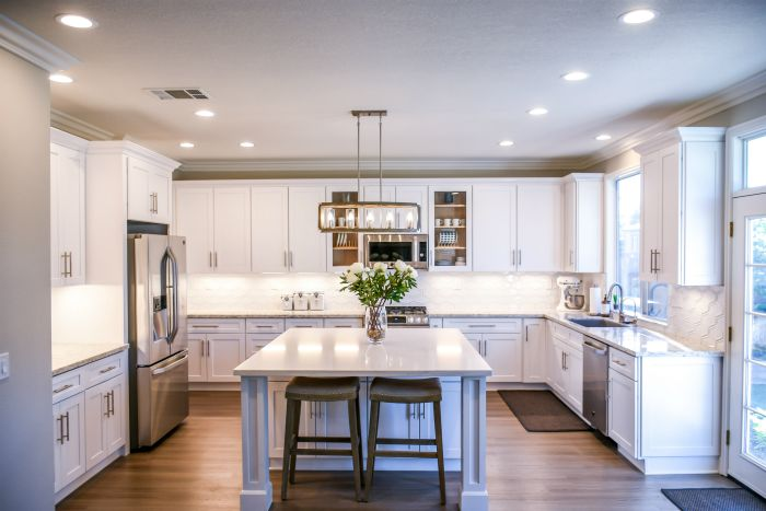 kitchen interior with white cabinets and center island with stainless steel appliences