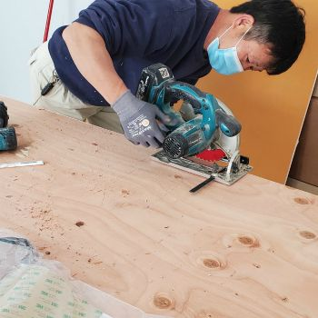 worker cutting wooden plant with circular saw