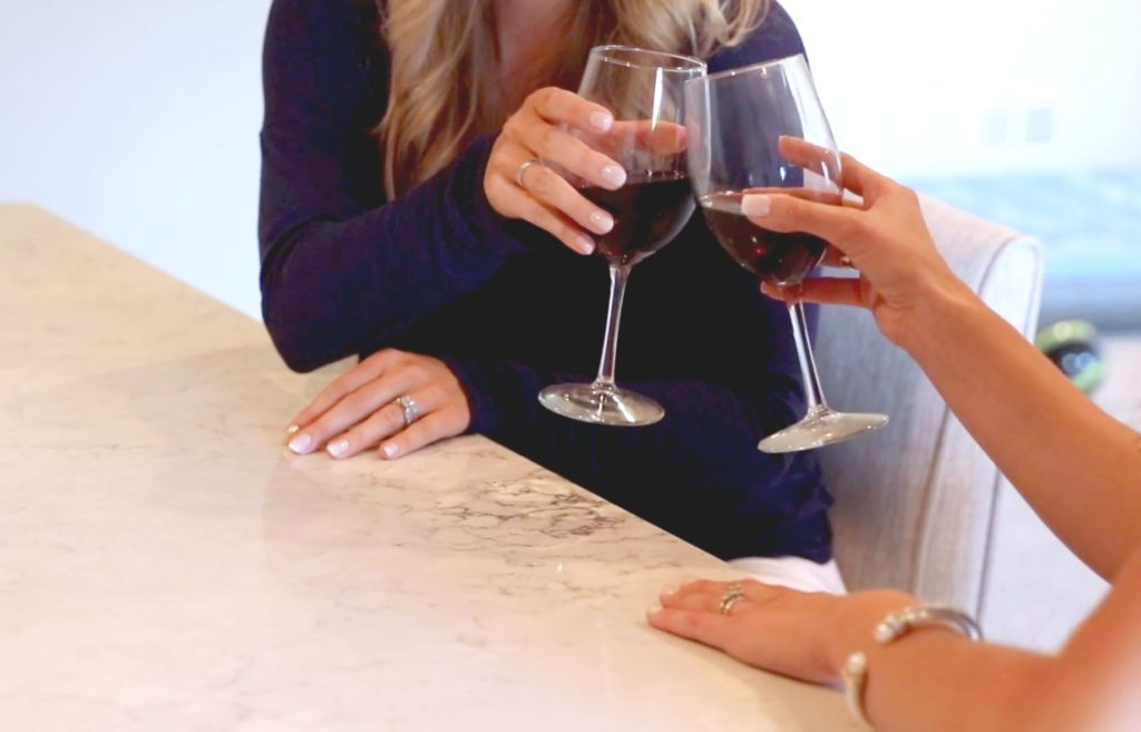 two women touching wine glasses while sitting at a stone countertop
