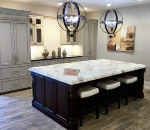 modern kitchen with white stone countertop and pull out barstools with black globe chandeliers