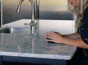 woman's hands holding coffee mug on stone countertop