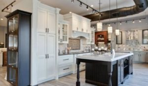 large modern kitchen with white cabinets and track lighting
