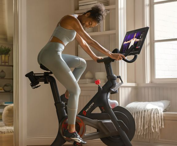 woman in athletic clothing riding a Peloton brand exercise bike indoors