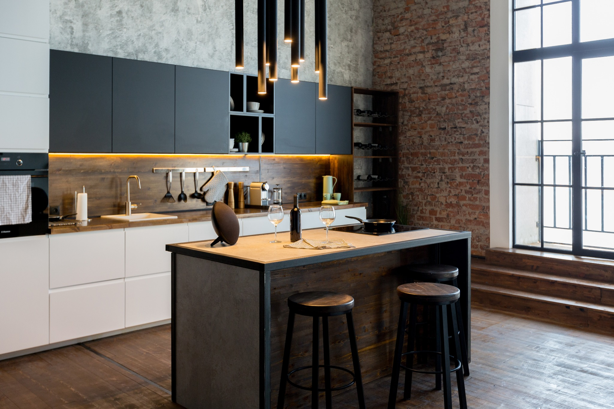 A warm and inviting looking industrial kitchen with built-in cabinets and a kitchen island.