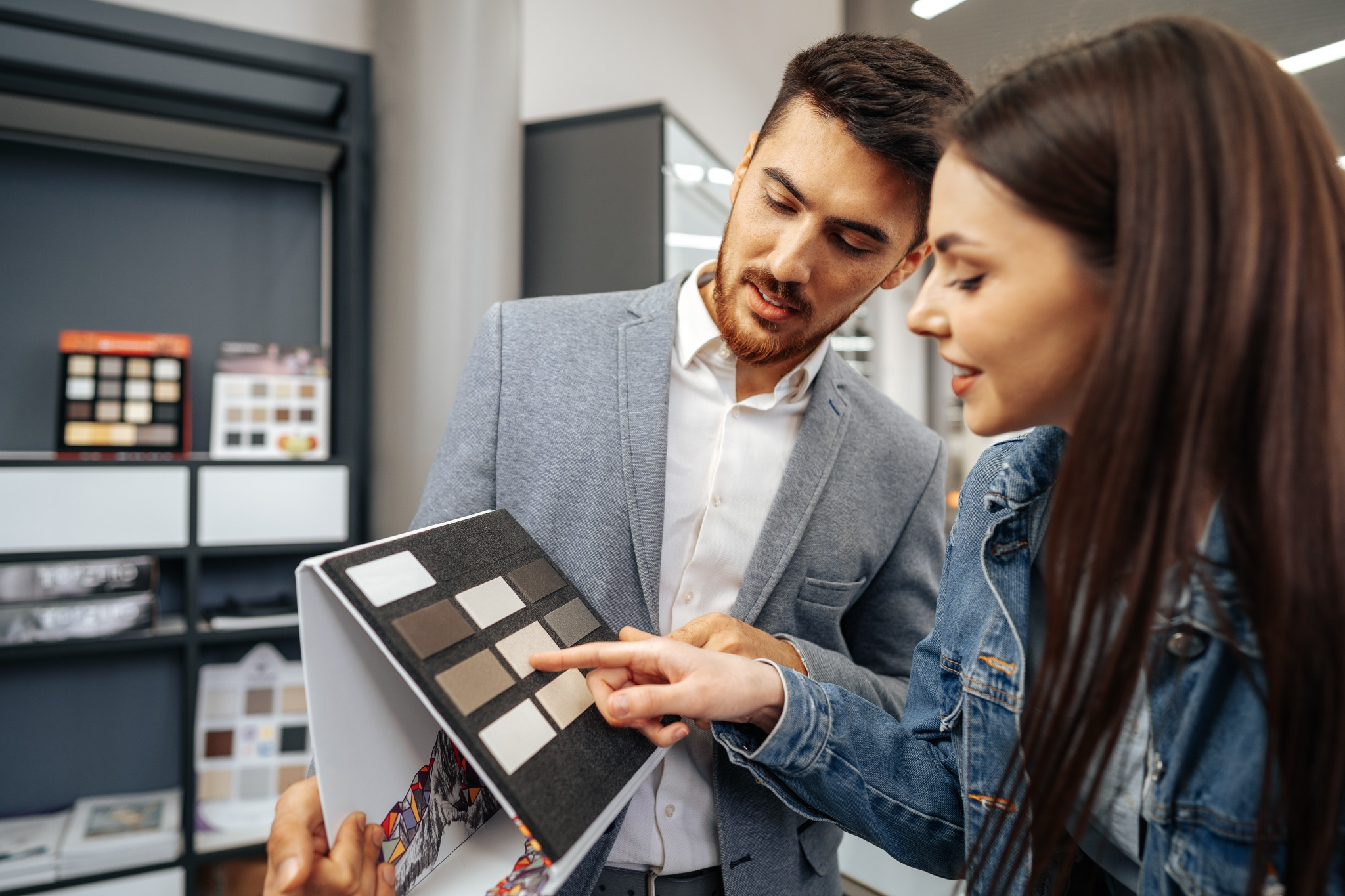 Woman selecting swatches for kitchen counter ideas with a salesperson.