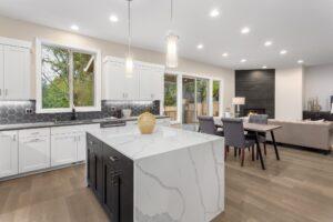 A kitchen with a granite waterfall kitchen island.