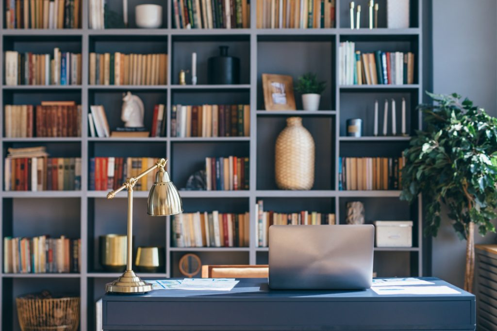 A luxury office with a style bookshelf behind the stone desk.