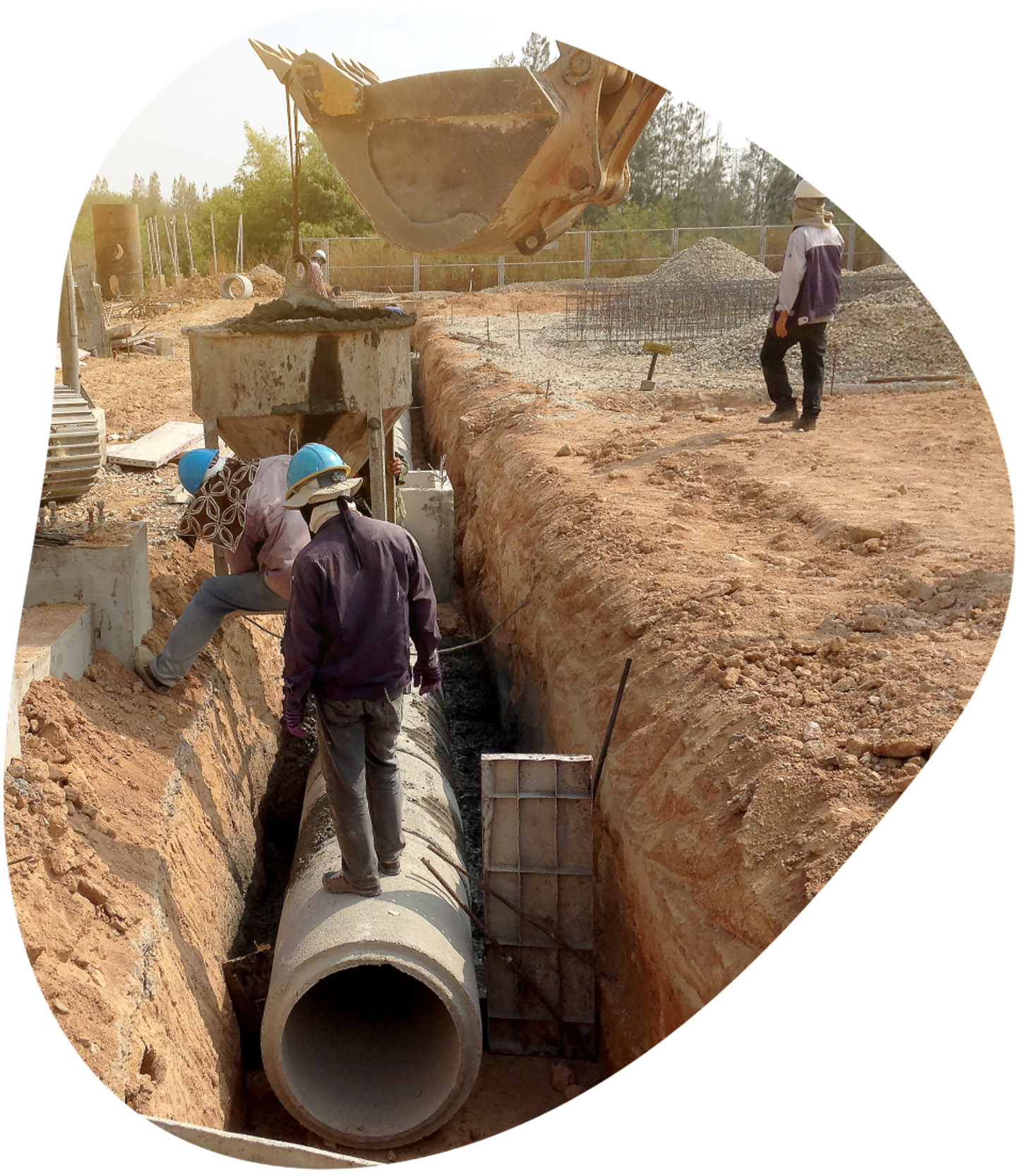 Workers standing on pipe in the road