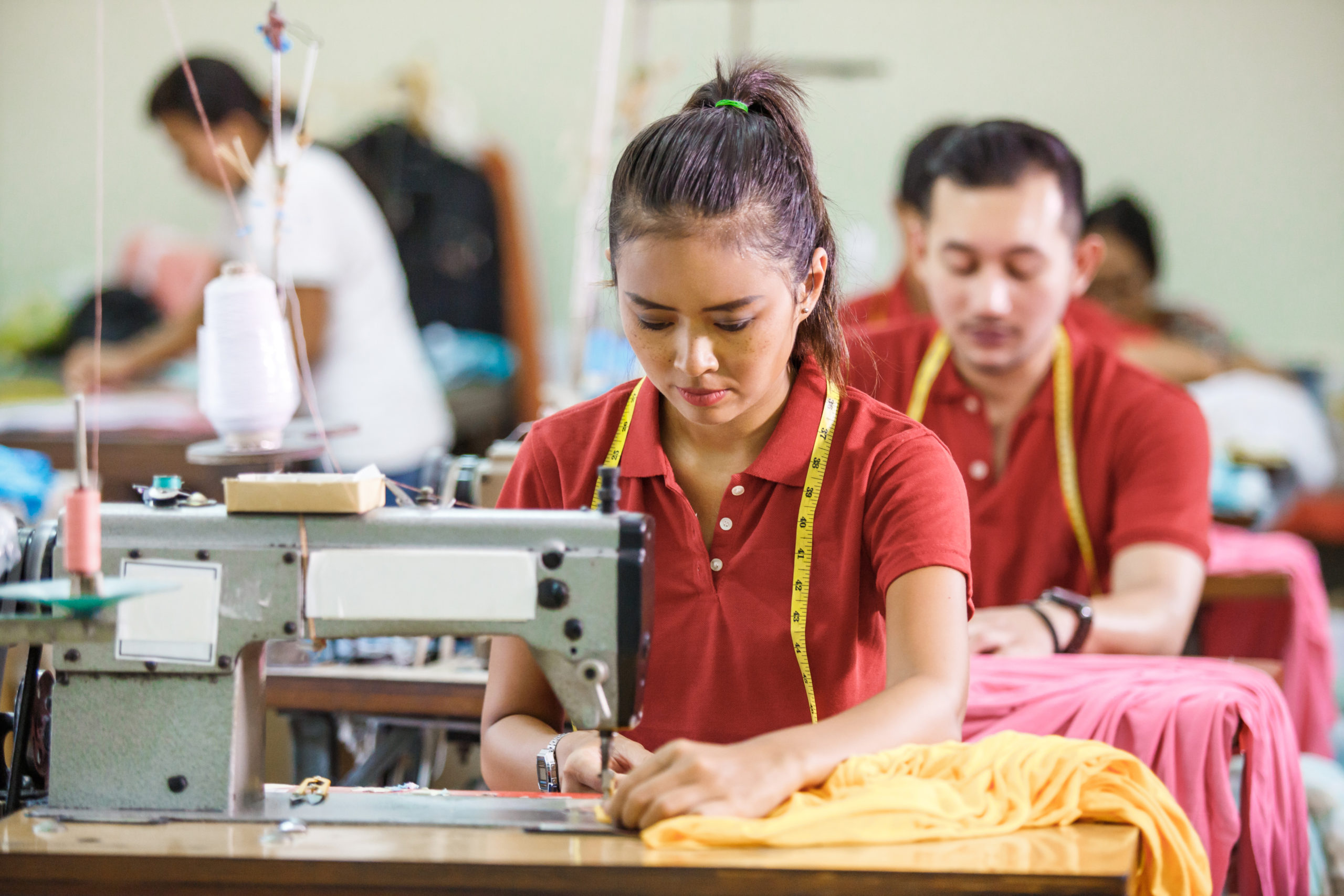 Garment workers operating sewing machine