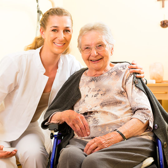 Young nurse and female senior in nursing home, the old lady sitt