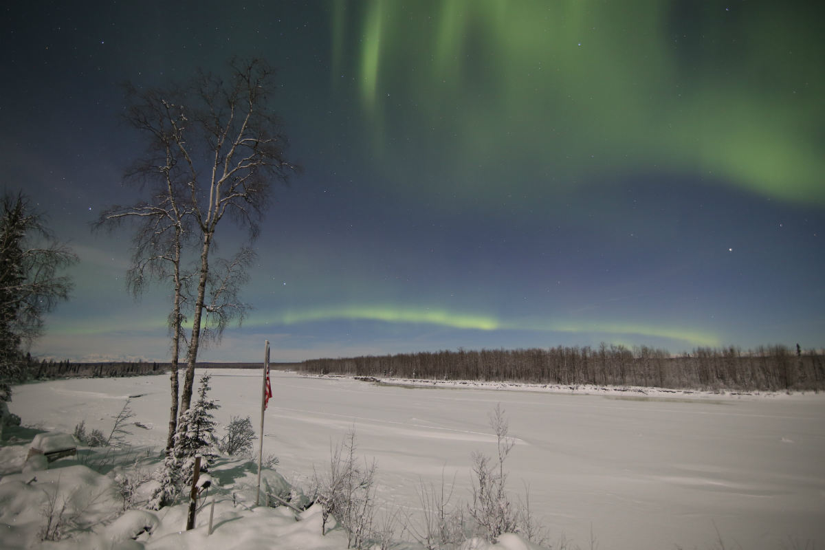 A wide area covered in snow and the aurora borealis above