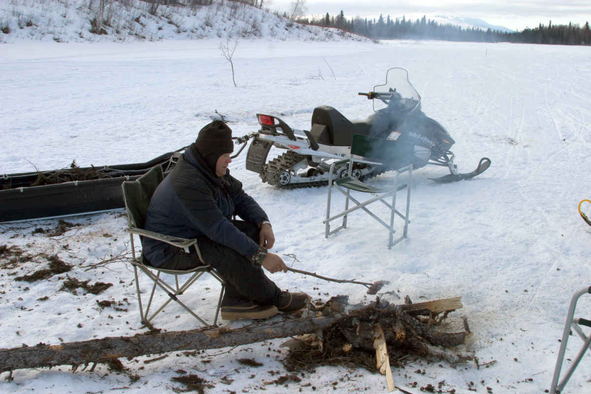 A man sitting and cooking something by the fire