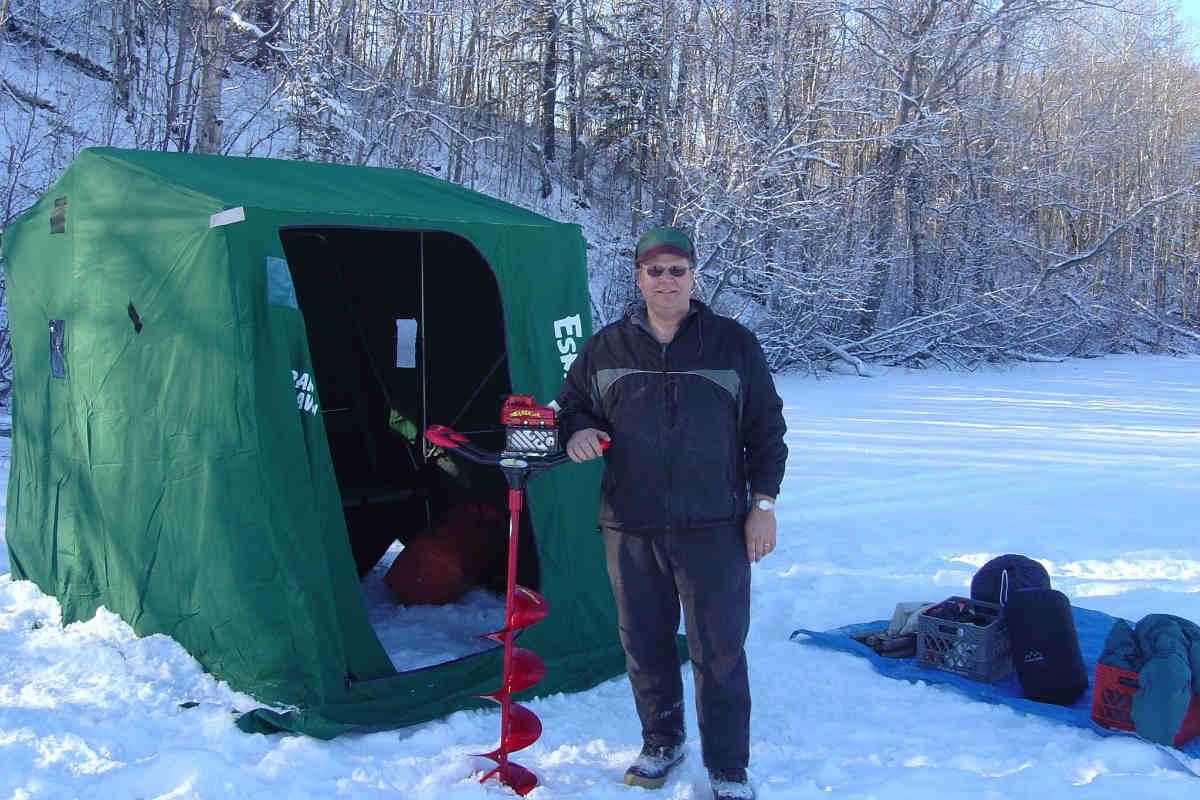 A man standing near a green tent