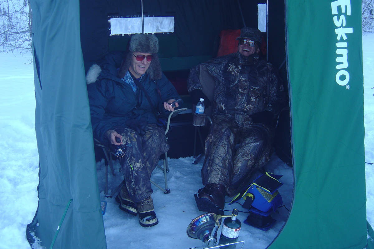Two men sitting and laughing inside a green tent