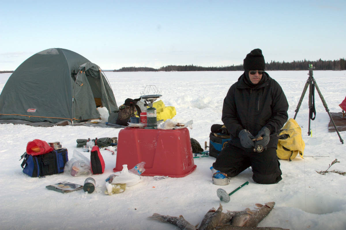 A man fishing on a hole in the ice and surrounded by his camping materials