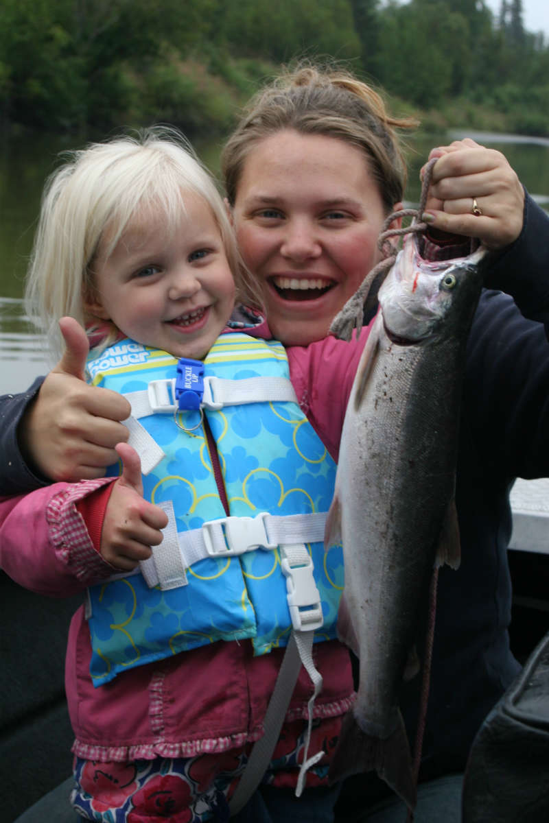 A woman and a young girl doing a thumbs up, the woman holding a fish