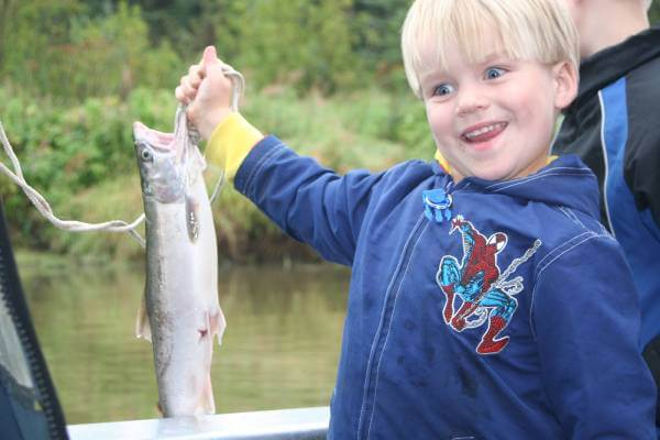 A young boy smiling while holding a fish
