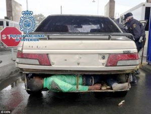 picture of man under car attempting to cross border