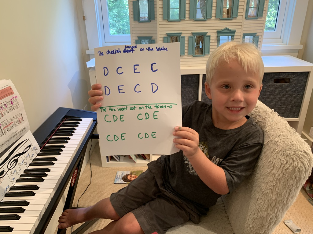 Young boy showcasing his worksheet during piano lessons