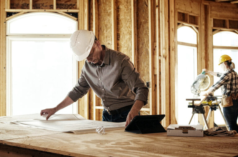 construction worker looking over plans